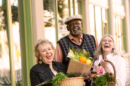 Laughing seniors returning with groceries from farmers market