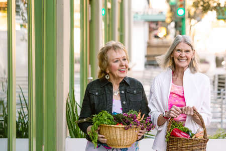 Two senior women returning from farmers market with produce