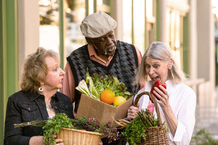 Three seniors with groceries from farmers market Banco de Imagens