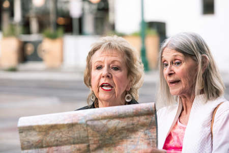 Two women in a city center checking road map