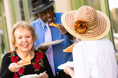 Three seniors downtown eating slices of pizza