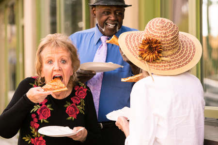 Three seniors eating slices of pizza downtown Banco de Imagens