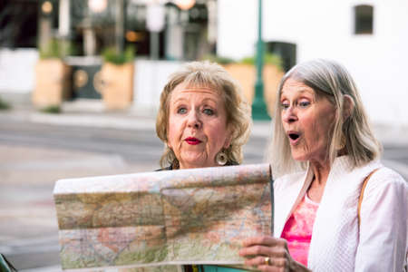 Two senior women in a city center checking road map