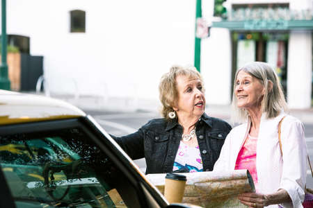 Two women in a city center holding road map