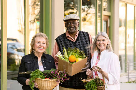Three seniors returning with groceries from farmers market Foto de archivo