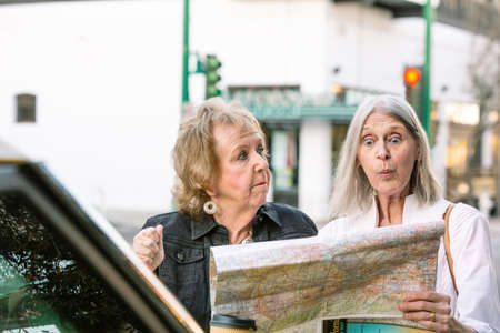 Two confused women in a city center checking road map Foto de archivo