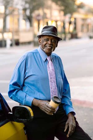 Handsome senior man smiling downtown and leaning against car Foto de archivo - 127924609