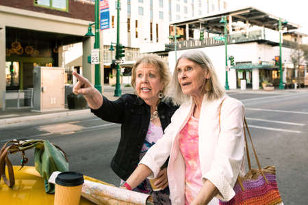 Two women in a city center consulting a road map
