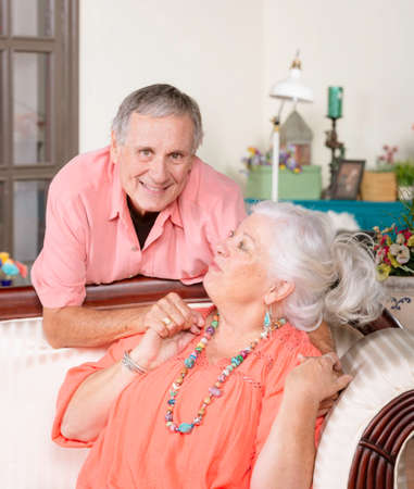 Senior man and woman at home on couch laughing Foto de archivo
