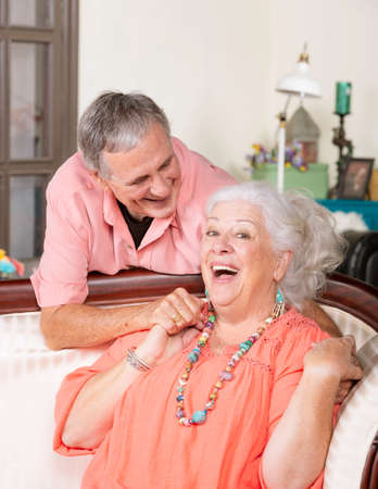 Affectionate senior man and woman at home on couch smiling Foto de archivo - 127924645