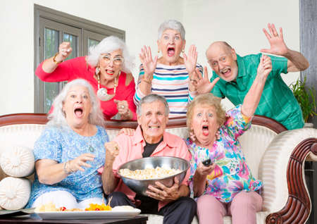 Six excited senior friends reacting to television Foto de archivo - 127924663