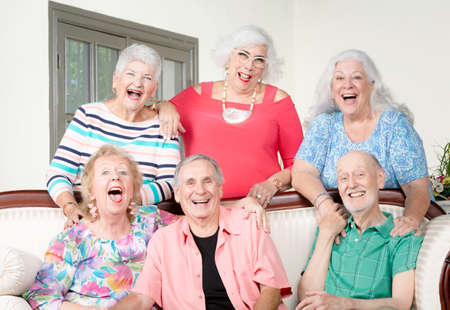 Six senior friends laughing out loud around an antique couch Foto de archivo