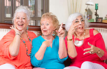 Three senior ladies in bright colored clothes vamping and posing