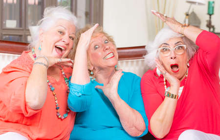 Three senior friends in bright colored clothes vamping and posing