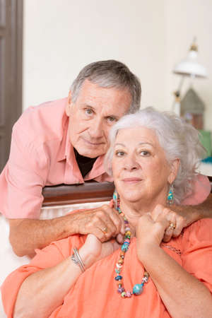Cheerful senior man and woman at home with neutral expressions