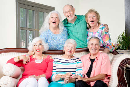 Six cheerful senior friends laughing around an antique couch Foto de archivo