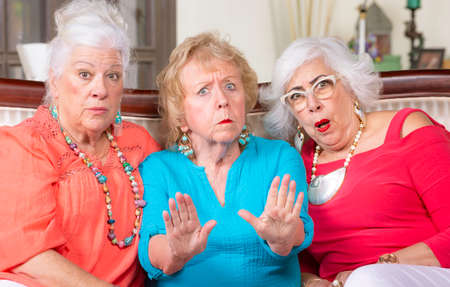 Three upset senior women expressing their displeasure Foto de archivo