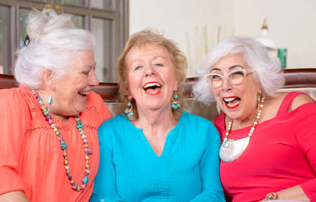 Three senior friends in bright colored clothes laughing