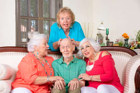 Three senior women giving affection to a surprised man