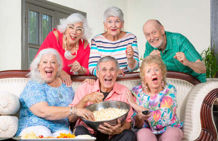 Six Happy senior friends reacting to television
