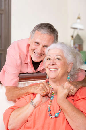 Cheerful senior man and woman at home holding hands Foto de archivo