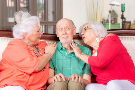 Two senior women giving affection to a nervous man