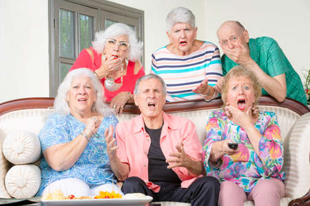 Six senior friends reacting to bad news television Foto de archivo
