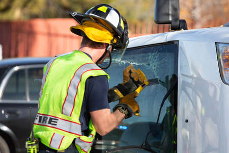 Emergency responder sawing through the window of a mini van at accident site Foto de archivo - 138389587