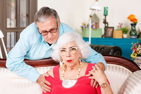 Worried senior man comforting woman at home