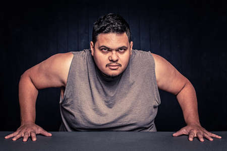 Angry Latino man with arms bared leaning in