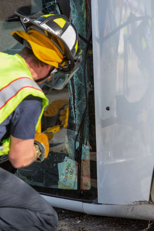 Vertical shot of mergency responder sawing through a mini van window at accident site Foto de archivo