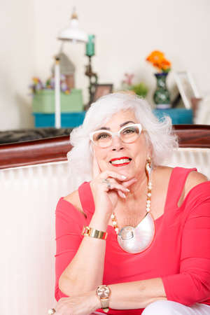 Fashionable senior woman in red top with bold jewelry Foto de archivo