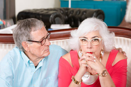 Worried senior man and woman at home embracing Foto de archivo