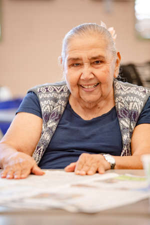 Cheerful Mexican woman in a senior activity center