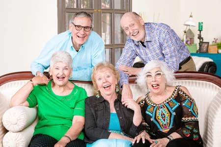 Five happy senior friends around an antique couch laughing Foto de archivo - 142915555
