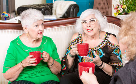 Three senior women having coffee or tea and a conversation together