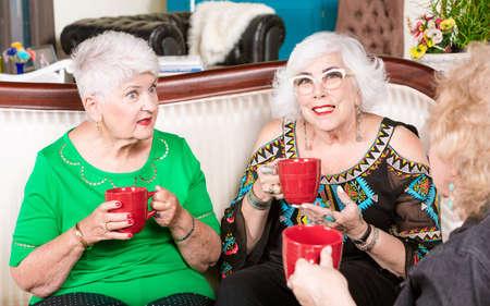 Three senior women having coffee or tea and a conversation together Foto de archivo - 142915559