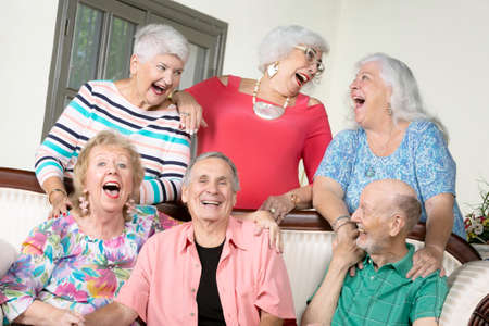 Six amused senior friends laughing out loud around an antique couch Foto de archivo - 142915560