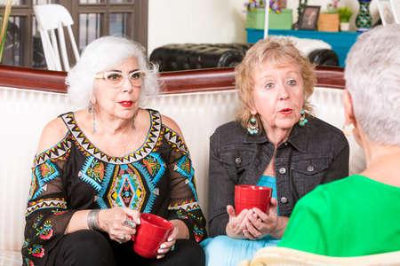 Three senior women enjoying a coffee or tea together Foto de archivo