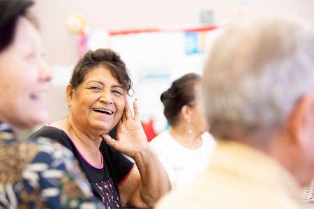Hispanic woman smiling and talking in a senior center Foto de archivo