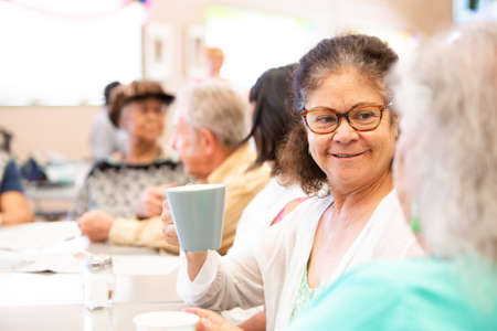Friends talking and having coffee in a senior center Foto de archivo