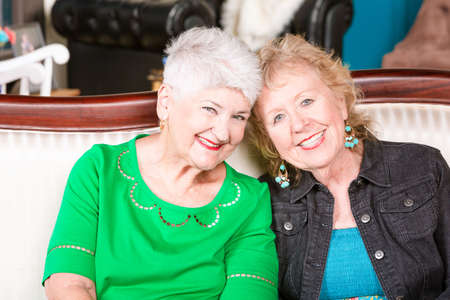Two senior women sitting together on a couch