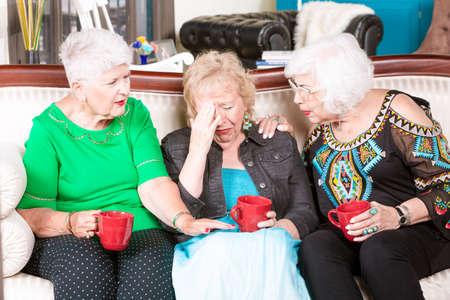 Two senior women support their upset friend Foto de archivo