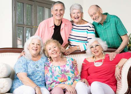 Six cheerful senior friends around an antique couch