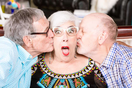 Two senior men kissing the same woman