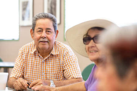 Hispanic man smilingwith friends in a senior center Foto de archivo