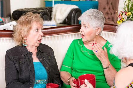 Three senior women together sharing shocking gossip Foto de archivo - 142915642