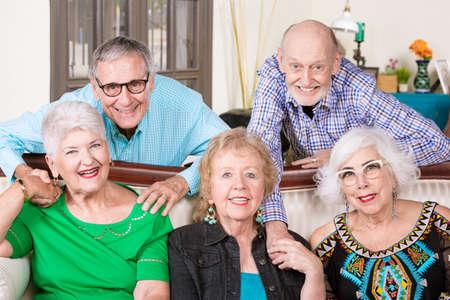 Five happy senior friends in a living room Foto de archivo