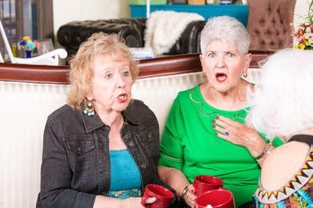 Senior woman reacting to hearing shocking gossipor news Foto de archivo
