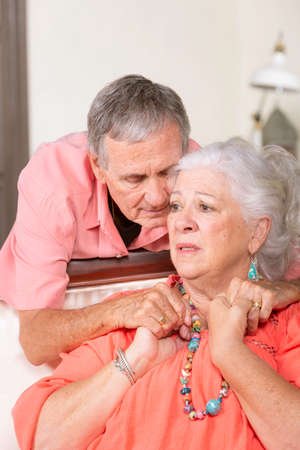 Upset senior man and woman at home embracing Foto de archivo